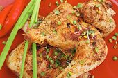 roast meat : chicken legs garnished with green sprouts and peppers on red plate isolated over white