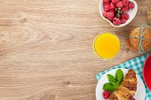 Healty breakfast with muesli, berries, orange juice, coffee and croissant. View from above on wooden