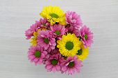 Yellow and pink Santini flower bouquet on white wood