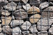 Rocks In Solid Metal Grid Wall Closeup