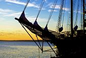 stock photo of tall ship  - Silhouette of the bow of a tall ship set against a sunrise sky - JPG