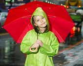 Young Girl Standing In Rain With Raincoat And Umbrella