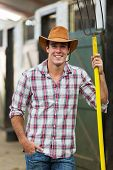 handsome cowboy holding a pitch fork in stable