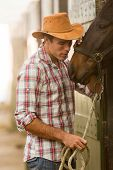 young cowboy whispering to a horse in stable