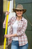 happy female farmer holding a pitch fork inside stable