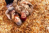 overhead view of happy young couple lying on autumn leaves