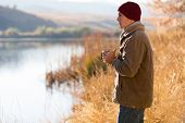 thoughtful man standing by lake and drinking coffee in autumn