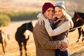 portrait of happy farm couple hugging in horse ranch