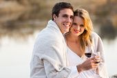 beautiful couple wrapped in blanket and holding glasses of wine at sunset