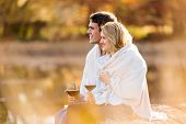 romantic young couple having red wine outdoors by the autumn lake