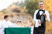 attractive waitress holding a bottle of wine in front of customers