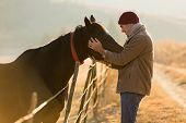 caring young man touching his horses in winter morning