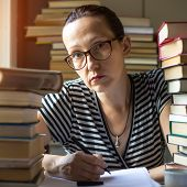 Intellectual woman writes on a notebook in a room with lots of books (loking at the camera)