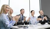 business, technology and office concept - happy business team with laptop computers, documents and c