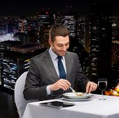 restaurant, people, technology and holiday concept - smiling man with tablet pc eating main course a