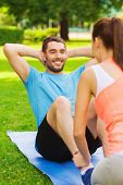 fitness, sport, training, teamwork and lifestyle concept - smiling man with personal trainer doing e
