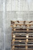 Closeup of a stack of wooden pallets against concrete wall