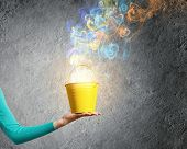 image of fumes  - Close up of female hand holding bucket with colorful fumes - JPG