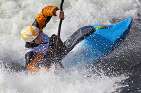 foto of kayak  - an active male kayaker rolling and surfing in rough water - JPG
