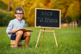 stock photo of schoolboys  - Cute little schoolboy feeling excited about going back to school - JPG