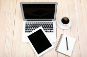 Open notebook, digital tablet, diary and a cup of coffee on wooden background, top view