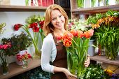foto of flower shop  - Young florist with fresh red tulips in the shop - JPG