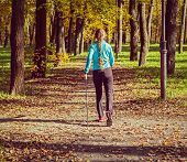 Vintage retro effect filtered hipster style image of nordic walking adventure and exercising concept - woman hiking with nordic walking poles in park