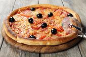 Tasty pizza with black olives and round knife on board and wooden table background