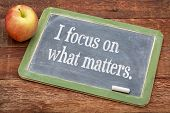 I focus on what matters - positive affirmation words on a slate blackboard against red barn wood