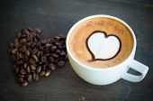 Cup Of Coffee With Latte Art And Heart Coffee Beans On Wooden Background