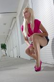Blonde squatting on white