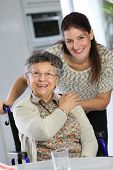 Portrait of elderly woman in wheelchair with homecarer
