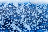 Snowflakes And Blue Frost On Glass In Winter