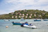 pic of ski boat  - Small boats and jet skis anchored bya tropical luxury resort - JPG