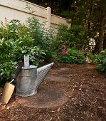 A Trowel And Old Watering Can Sit On A Stone Path In To The Woods