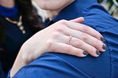 Hand of a woman on a man`s shoulder with engagement ring