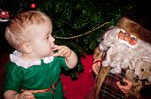 stock photo of santa baby  - Little baby biy sits under decorated Christmas tree with Santa - JPG