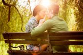 pic of sitting a bench  - Young couple in love sitting on a park bench photographed from the rear illuminated background sunlight passionate look at each other in the moment before the kiss - JPG