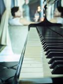 picture of grand piano  - Black piano with blurred woman reflected in the piano - JPG