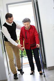 foto of crutch  - Man helping elderly woman with crutches - JPG