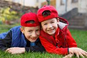 stock photo of laugh  - Little boys laughing in grass at backyard  - JPG