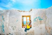 pic of abandoned house  - Young woman sitting on the window with sea view in abandoned house - JPG