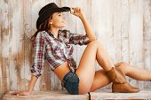 image of cowgirls  - Beautiful young cowgirl adjusting her hat and smiling while sitting against the wooden background - JPG