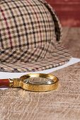 pic of private investigator  - Deerstalker or Sherlock Hat and magnifying glass on Old Wooden table - JPG