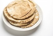 stock photo of pita  - Brown pita bread in a plate on white background - JPG