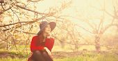 image of redhead  - Portrait of a beautiful redhead women in red sweater and hat with cup in blossom apple tree garden in spring time on sunset - JPG