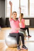 stock photo of pregnancy exercises  - Young pregnant woman doing exercise using a fitness ball - JPG