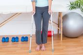 stock photo of crutch  - Woman standing with crutch in medical office - JPG