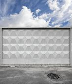 pic of manhole  - Dark urban road pavement with sewage manhole and blue sky behind gray concrete fence - JPG