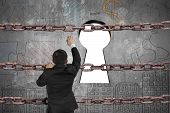 picture of keyholes  - Businessman climbing on old iron chain for keyhole door with blank white view and business concept doodles wall background - JPG